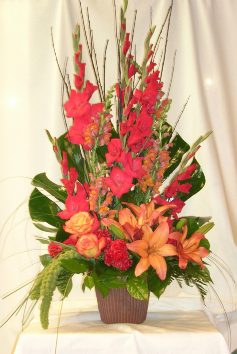 Altar arrangement in orange tones with gladiolas, lilies, snapdragons, and roses.