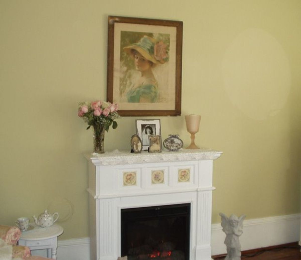 The electric fireplace has rose decals added. Mantel decorations include an antique vase, bride photos, and a vase of pink roses. Above the fireplace is a old portrait.