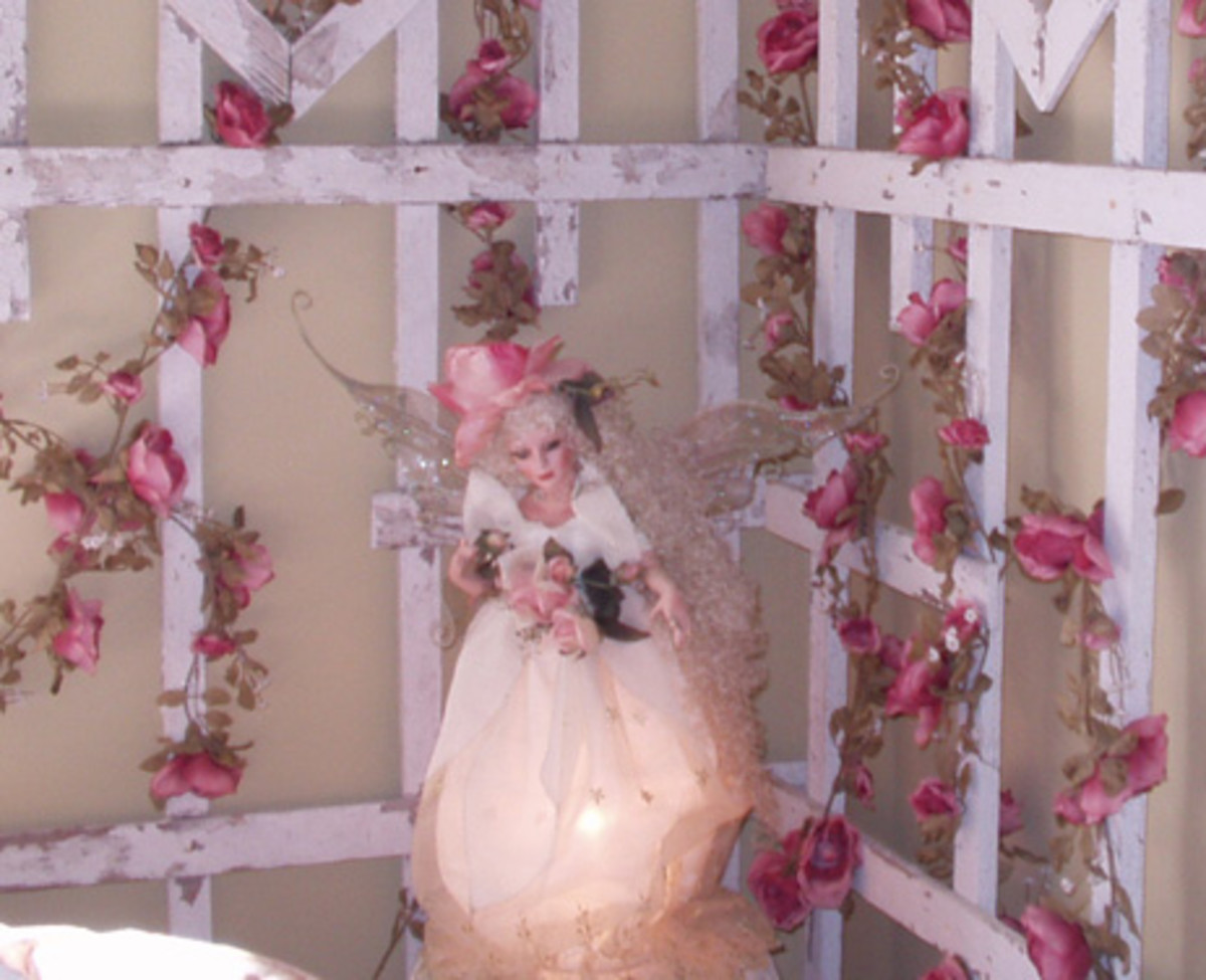 Can you believe this is a lamp? This homemade lamp was found at a local consignment shop and is the perfect accessory to a romantic cottage bedroom. The pretty fairy has a rose hat and is holding a bouquet of roses.