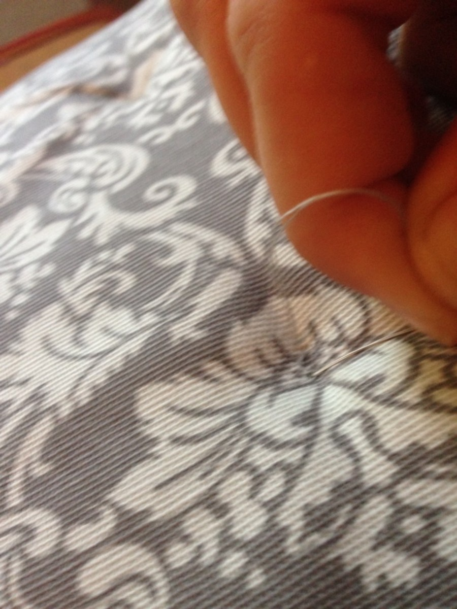 Thread is gently, but tightly, pulled to create an indent in the cushion.