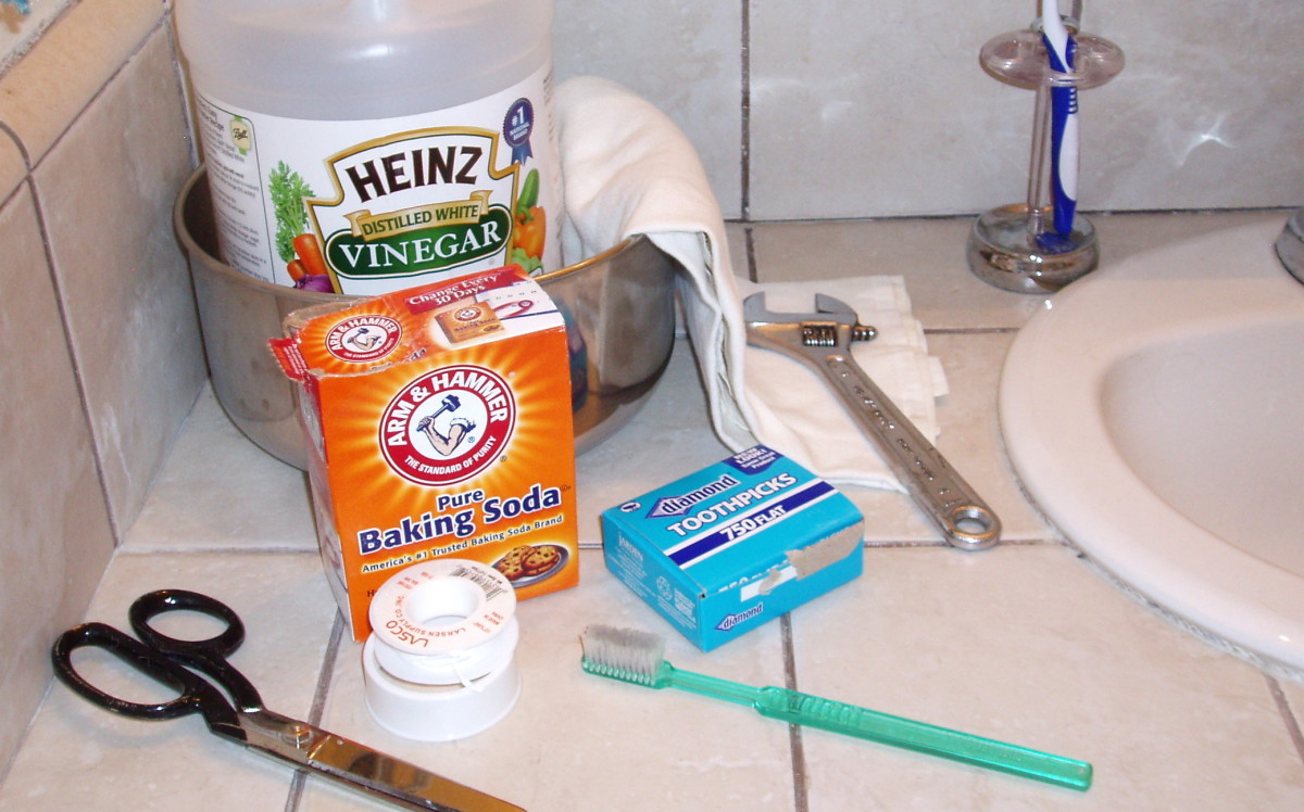 Shower head cleaning supplies: Bowl, vinegar, crescent wrench, soft cloth, baking soda, toothpicks, toothbrush, plumber's tape, and scissors to cut it.