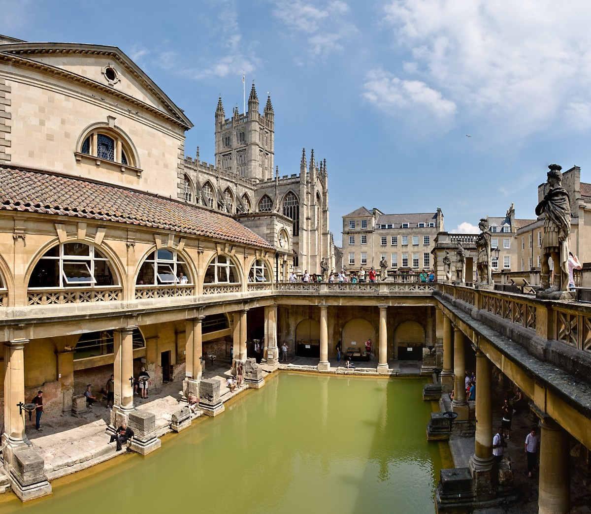 The Great Bath in the city of Bath, England; the bath, the light grey base of the surrounding pillars, and the passageway date from Ancient Roman times