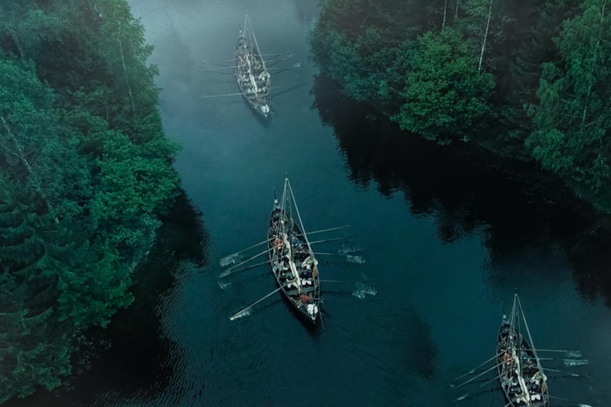 Medieval reenactment of Viking row boats navigating a river.