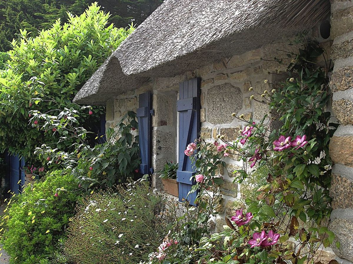Roses and clematis grow up around the stone dwelling.