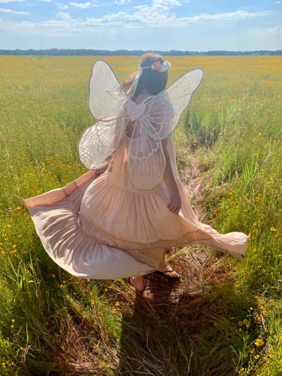 A woman is wearing a fairy costume complete with wings and a garland of flowers on her head.