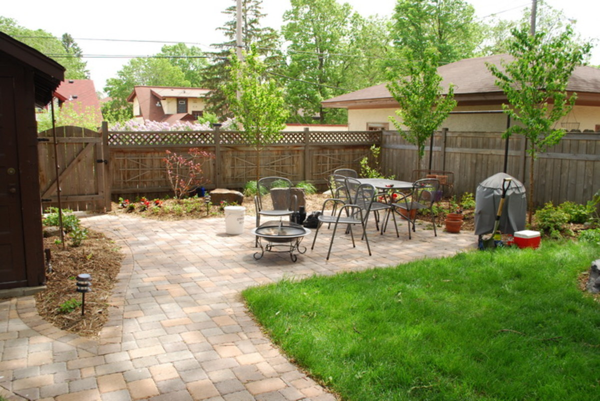 Pavers take over the backyard with a patch of green grass