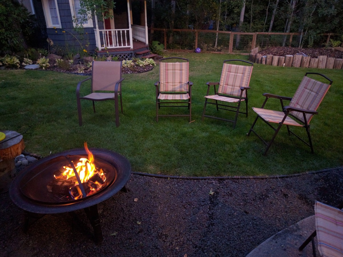 Seats on the grass surrounding a pea gravel and rubber edging firepit area