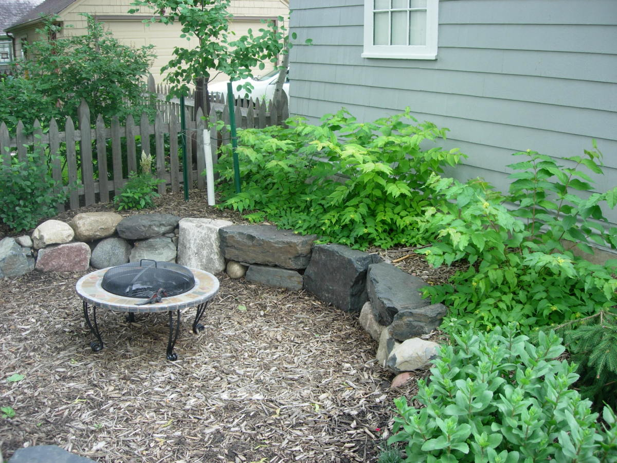 Mulch patio with a boulder edging that serves as seating.