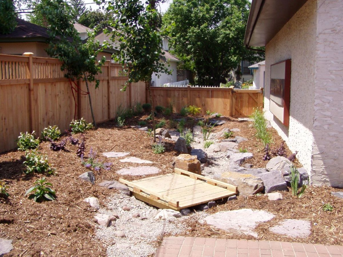 Mulch with stones and a little wooden bridge.