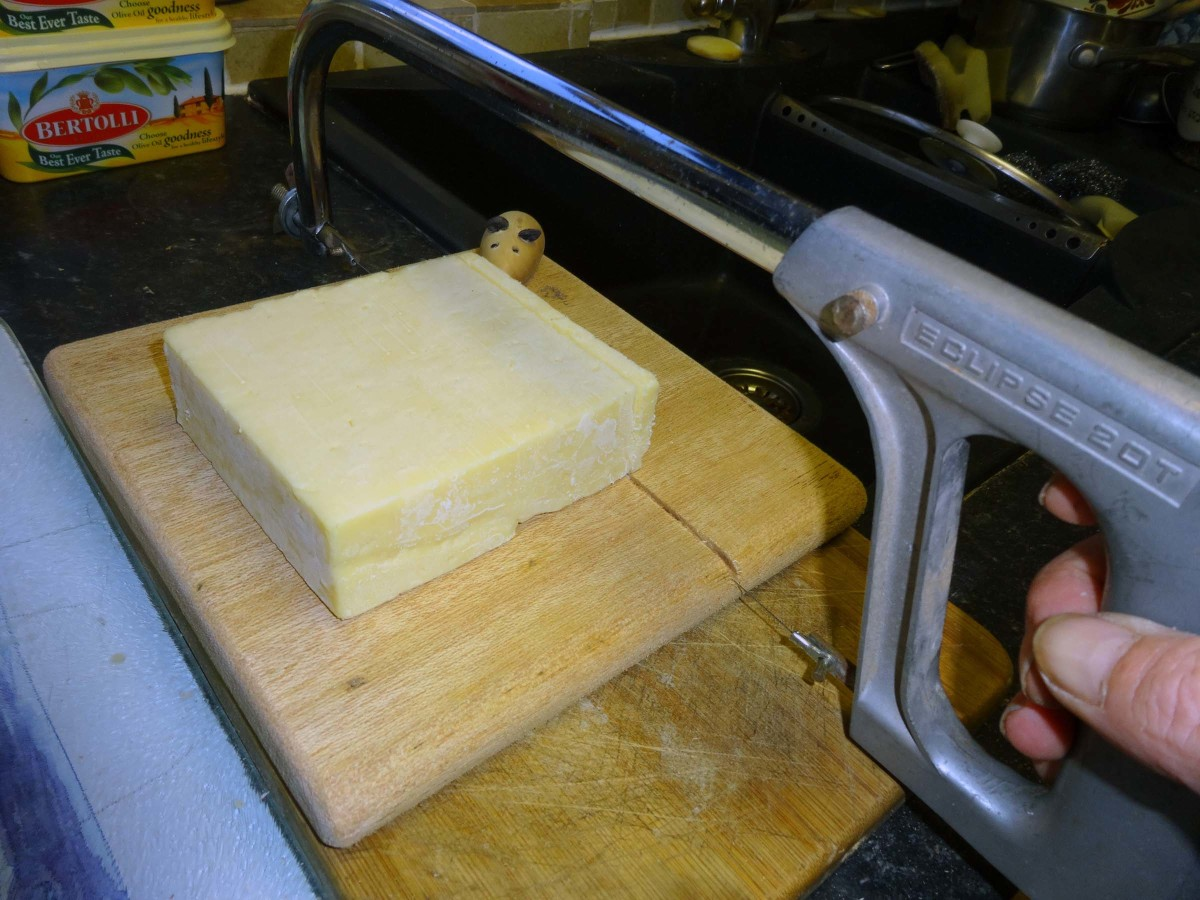 Cutting cheese with a hacksaw fitted with cheese wire.