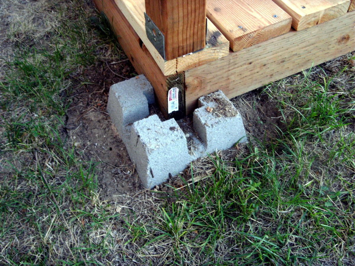 The new concrete pillar set into the ground for support.