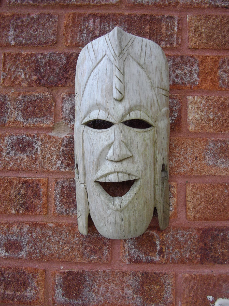 Mocking mask hanging on a red brick wall.