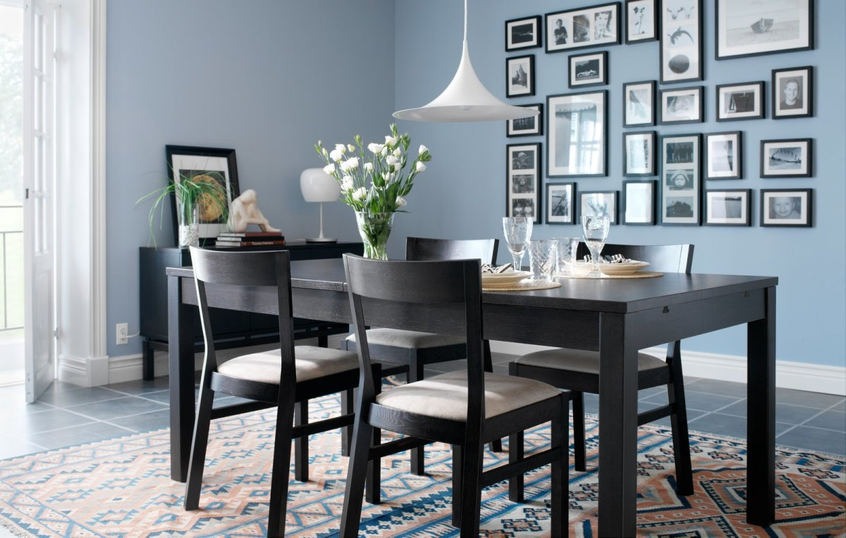 Framed photographs of all different sizes are used to create an attractive collage on this dining room wall.