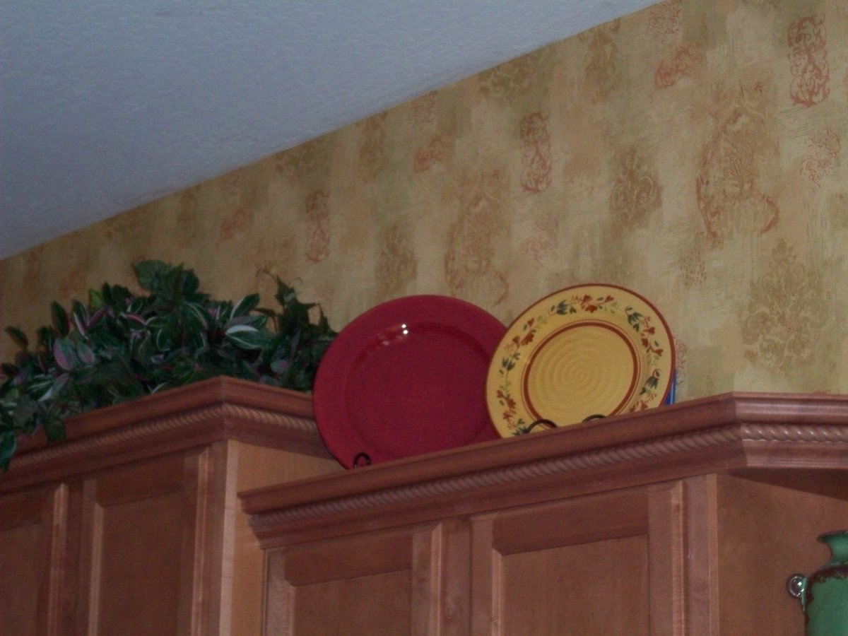 Display your favorite serving pieces above kitchen cabinets.