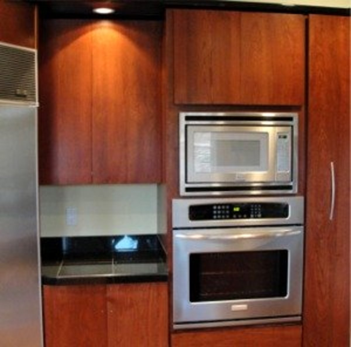 microwave oven on an oven wall with cabinets