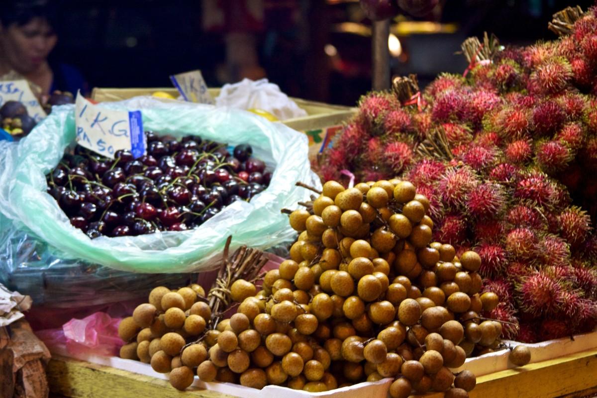 Cherries, Cat's Eye fruit, and Rambutan in a Kuala Lumpur market stall.