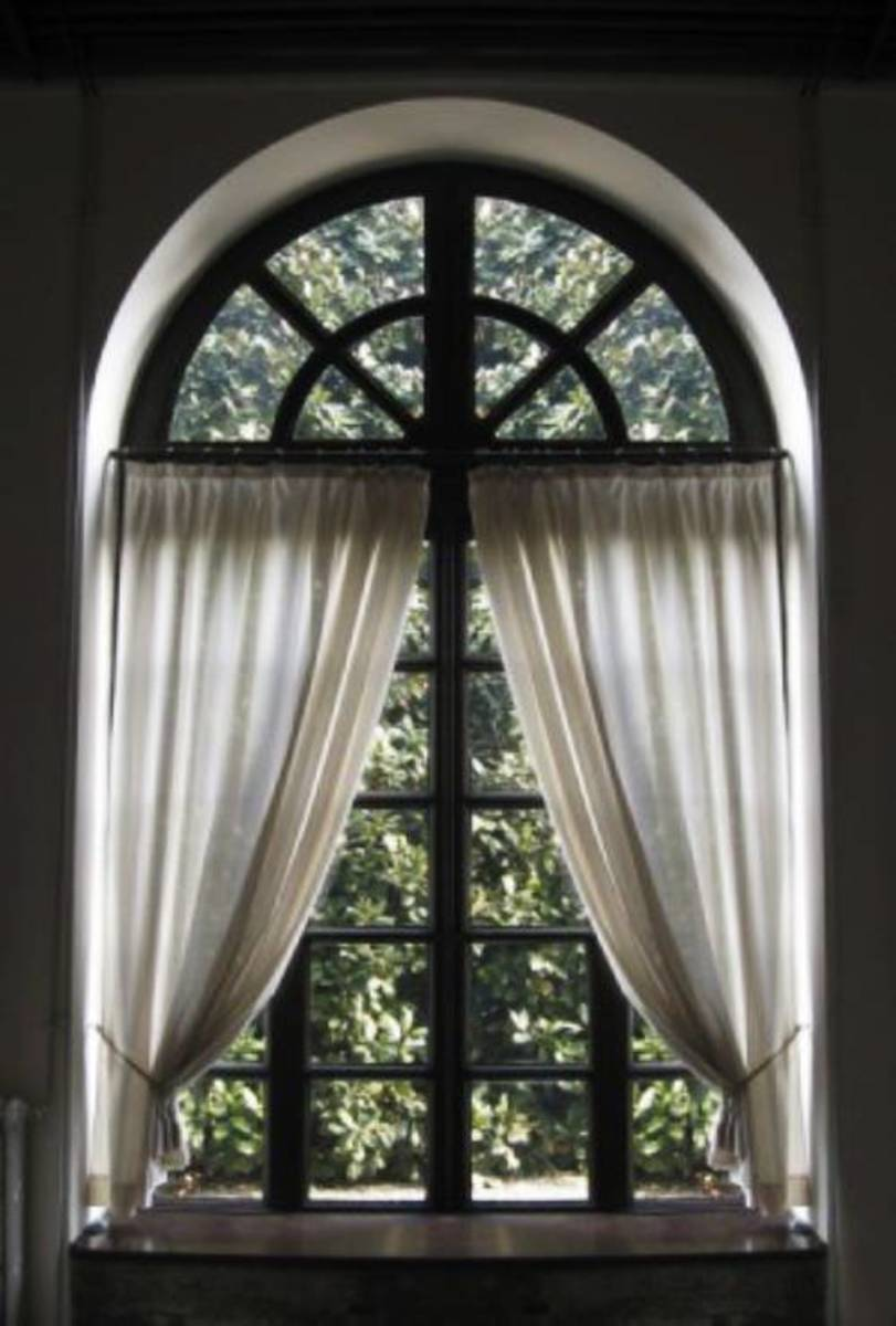 Install a straight rod across the bottom of the arch and use ready-made curtain panels.