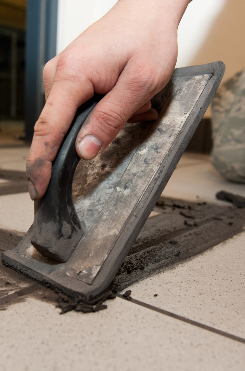 Hold the grout float at a 45-degree angle to the tile floor. Press the grout firmly into the joint.