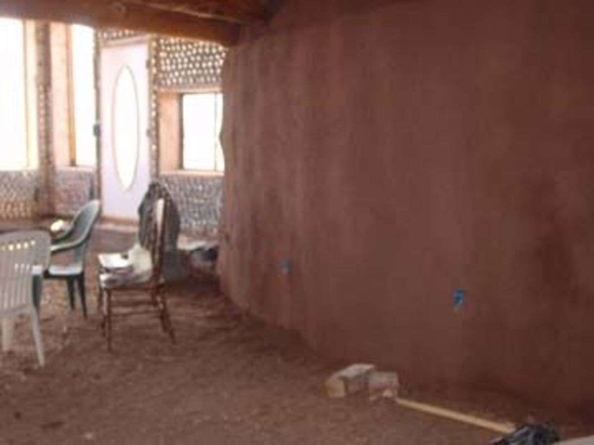 Mud application to rammed earth tire walls.