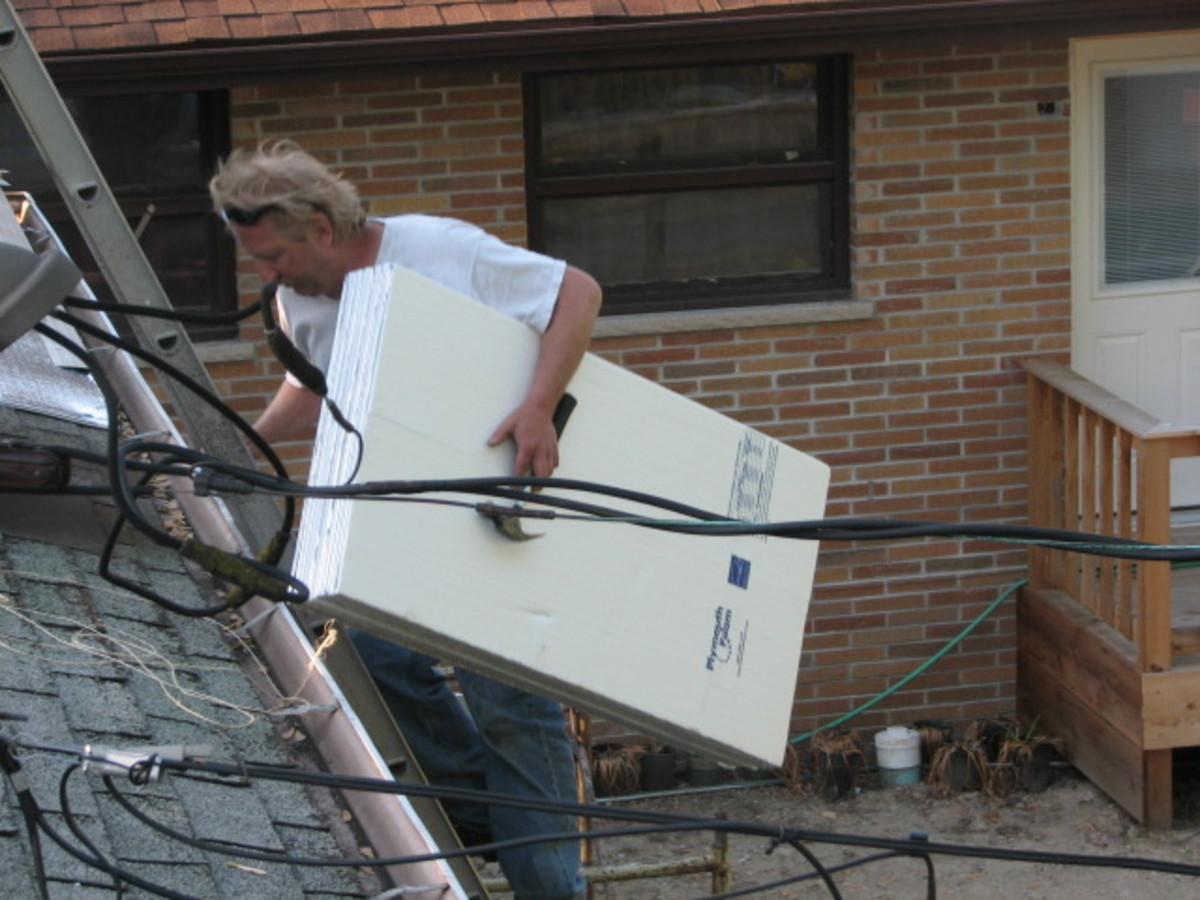 David carries foam sheeting to lay on top of the old asphalt shingles