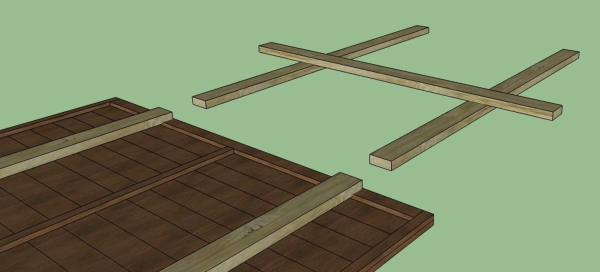 The legs for your panel will end up being an 'H' shape that the panel will sit on. Position two of lengths of wood on the ground parallel to each other, the same distance apart as the two that are nailed in place.