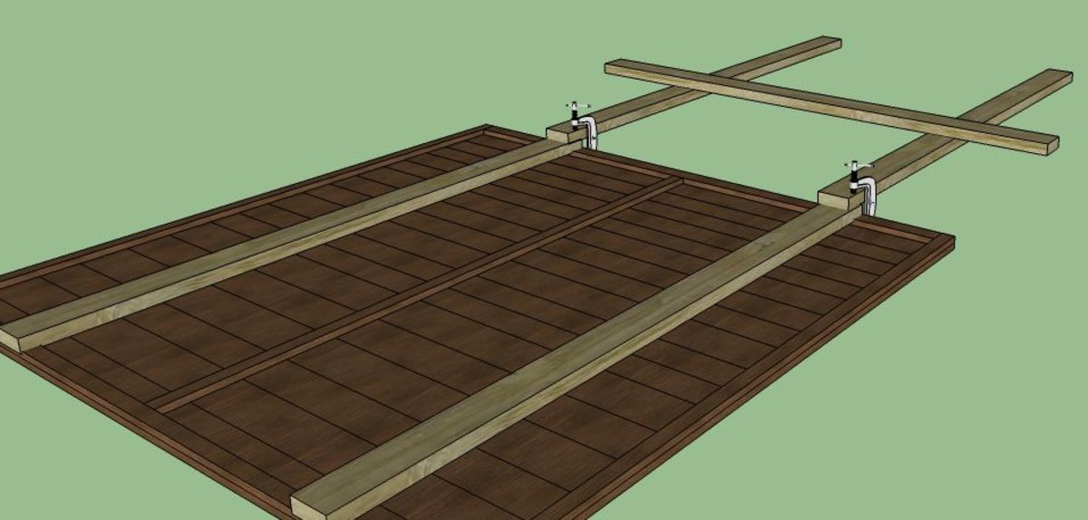 """Now clamp the """"H"""" shaped legs to the bottom of the lengths of wood you nailed to the panel.  Remember that the side facing up is the side that will be facing you, so be sure the clamps are easy to remove."""