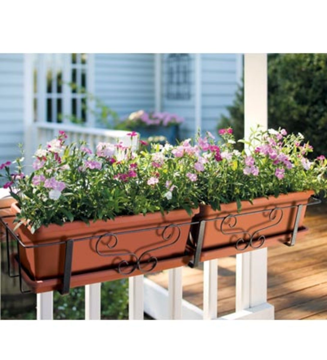 Terracotta colored plastic boxes, hung from the balcony railing, can bring color to any balcony.