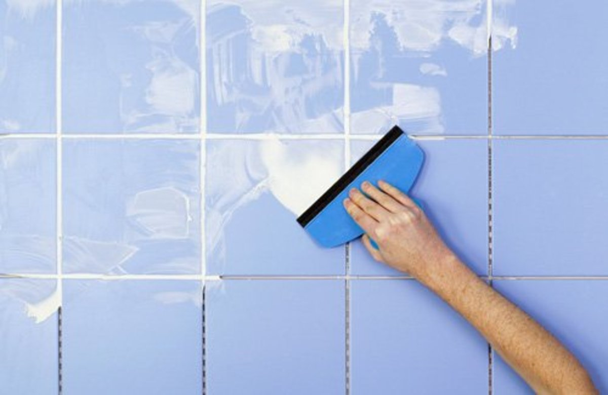 Applying white grout mix to a wall with blue tiles.