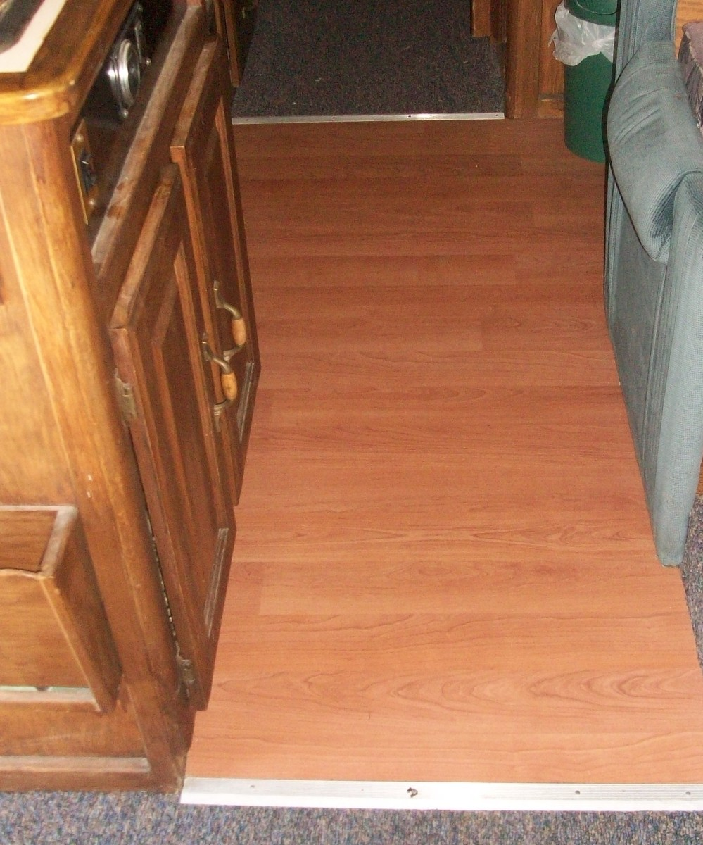 RV kitchenette floor with no trim on the sides, carpet trim on the ends of the area