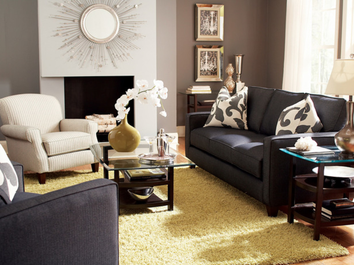 The gold of the area rug and vase here really make the couches pop, as well as the oversized pillows and wall colors.