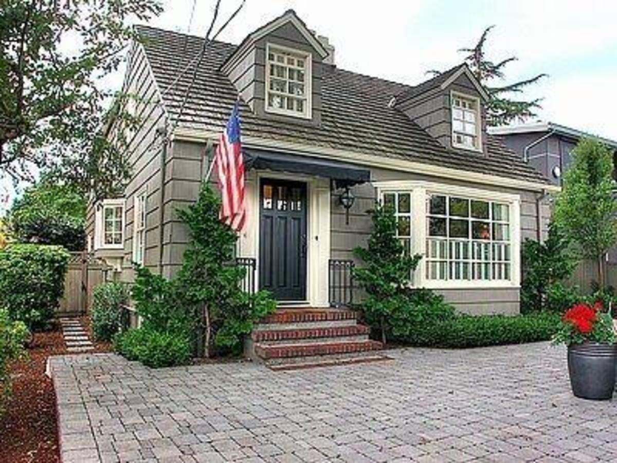 With Brick Steps And Bay Window Two Dormer Windows An American Flag