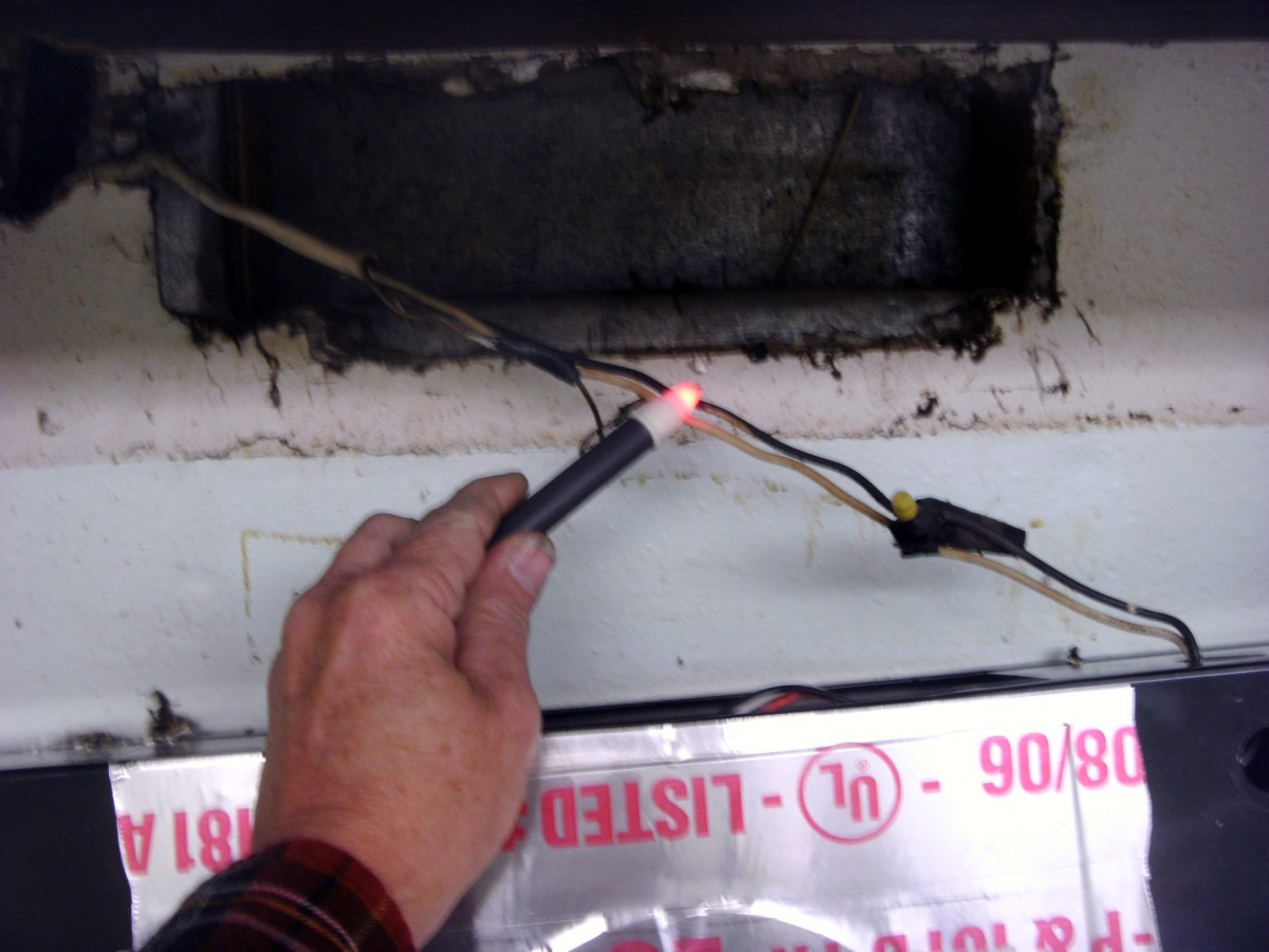 """Checking the power - this wire is hot and must be shut off at the circuit breaker.  The lower area with silver tape is the """"up"""" side of the old fan."""
