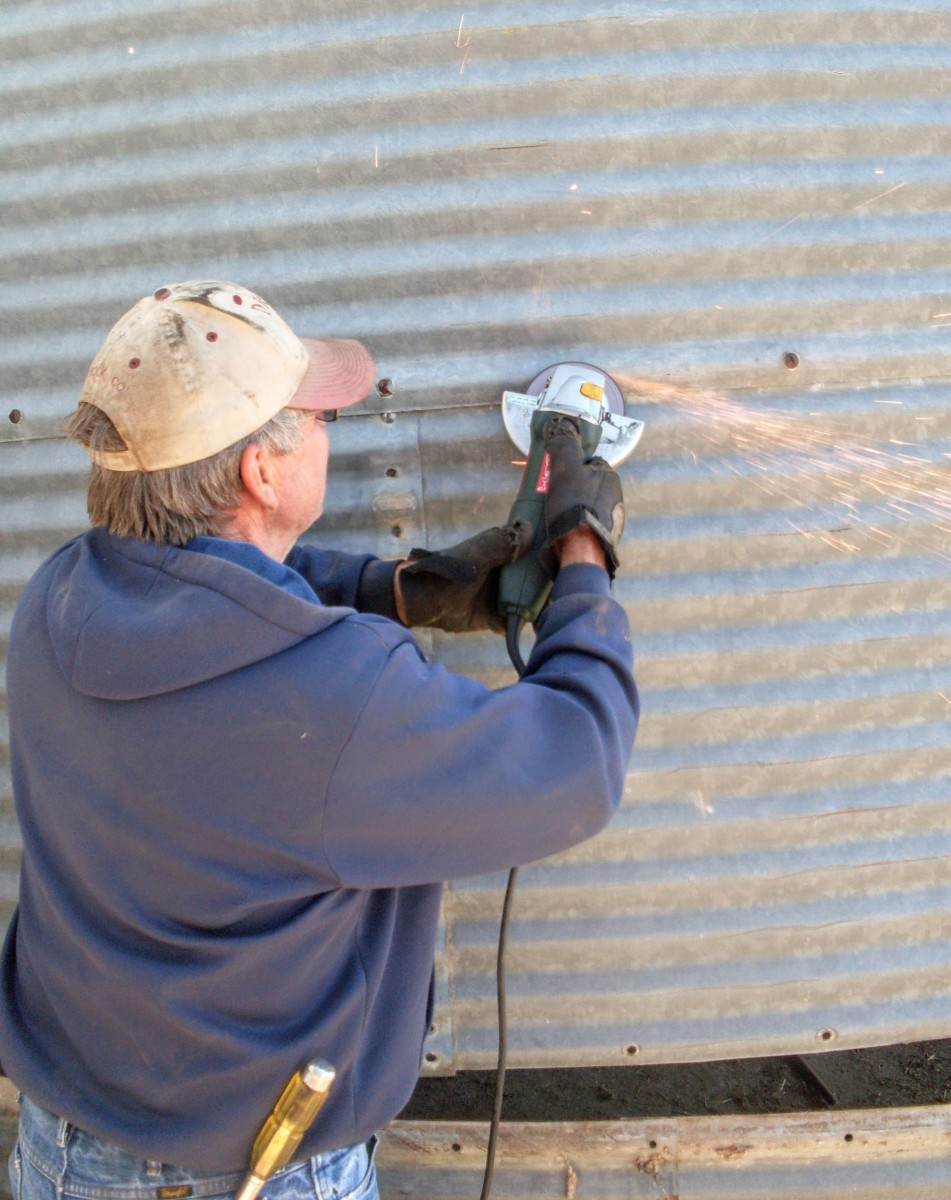 An angle grinder is used to remove stubborn bolt heads on this 1940s era grain bin which is to be moved.