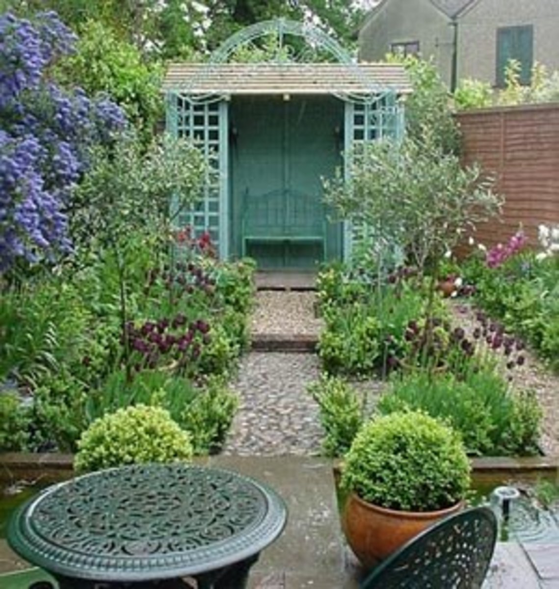 teal aqua potting shed with lush gardens