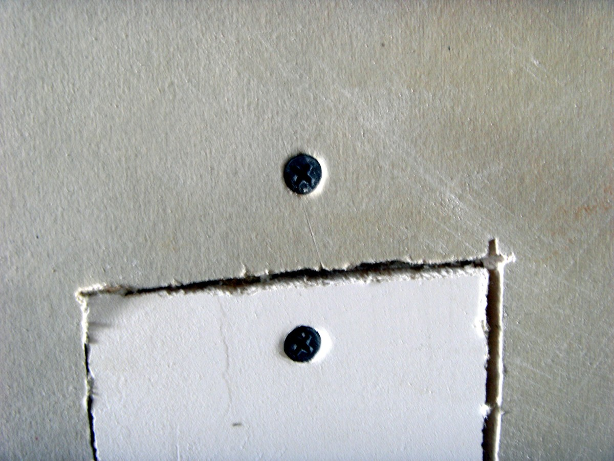 Closeup of the screws, showing them sunk just slightly into the drywall.
