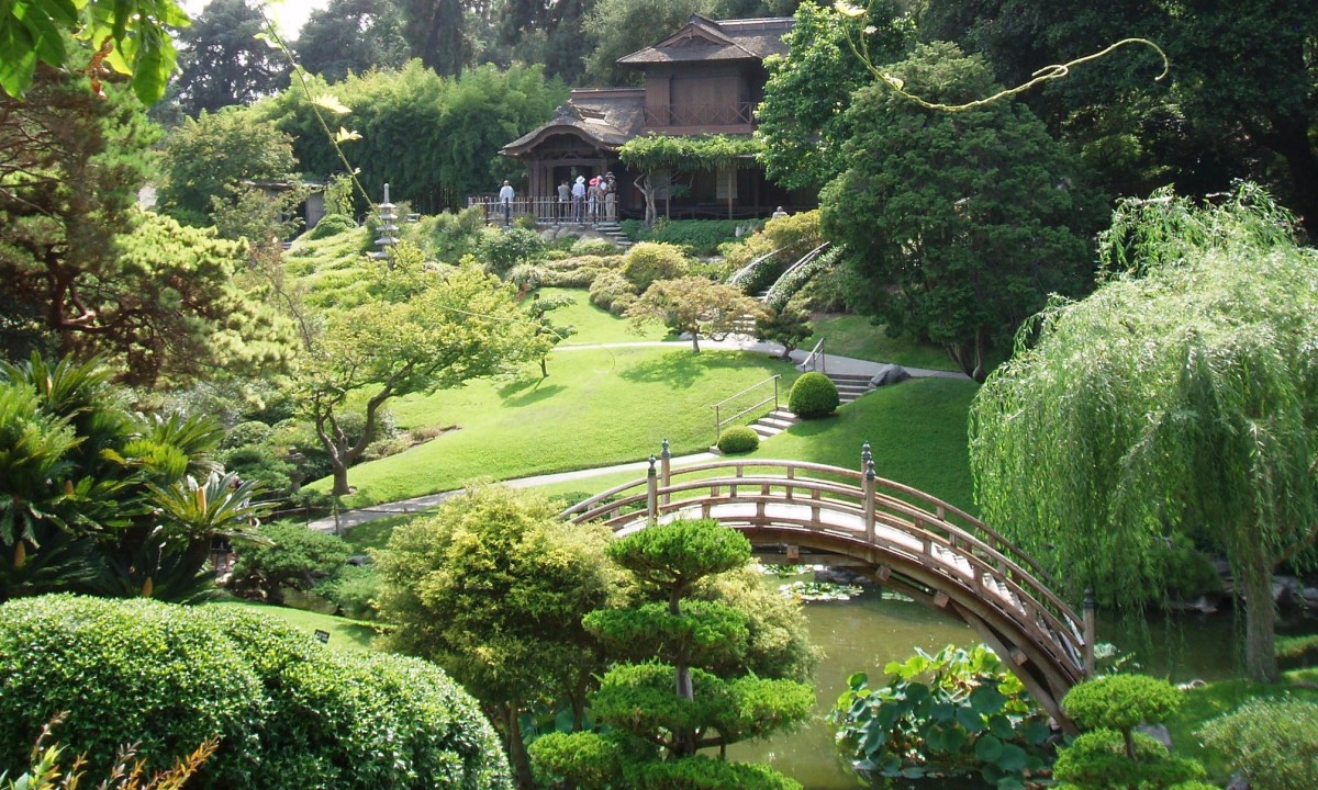 Japanese Zen––typified by peaceful, curving shapes of green rolling hills, round-canopied trees and bushes, and bridges over streams of slow-moving koi.