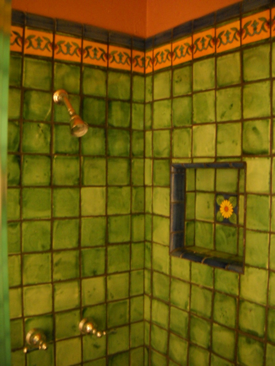 Green watercolor talavera tile in shower with yellow border and inset for shampoo.