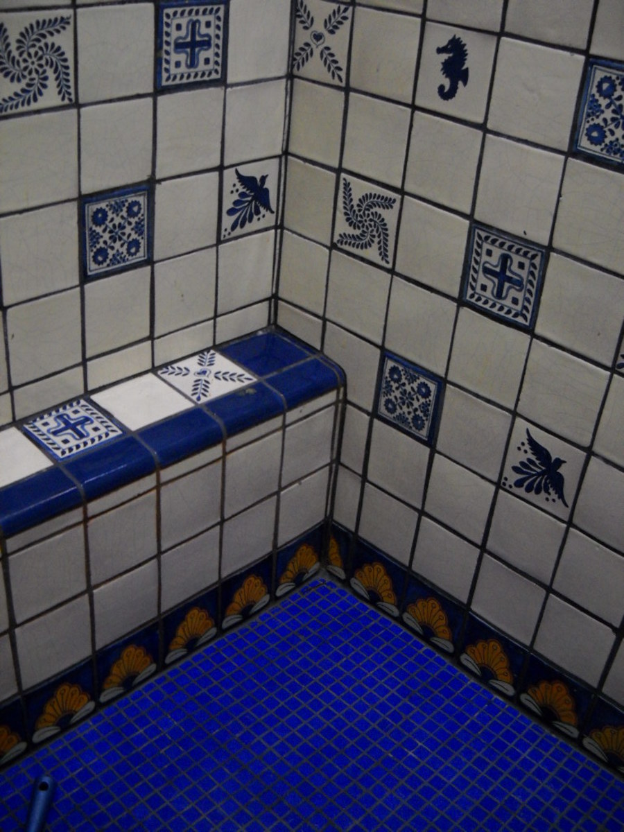 White and blue talavera tile shower with border and glass tile bottom.