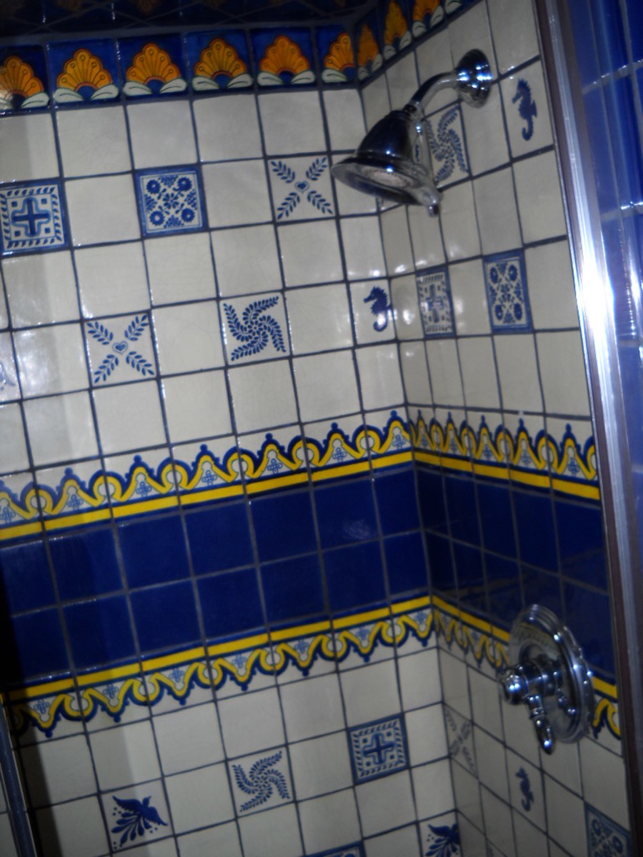 White and blue talavera tile shower showing middle border with patterned single tiles on white.