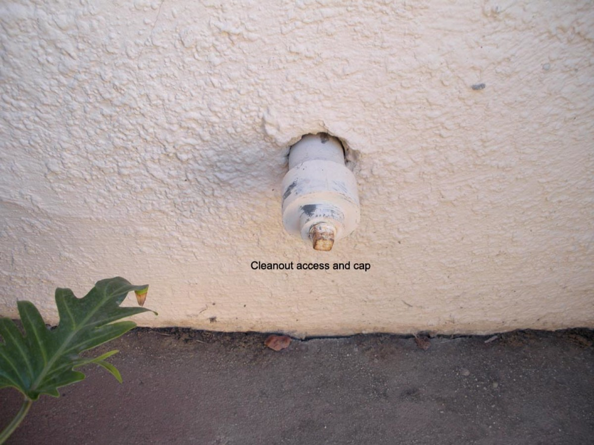 Cleanout access through house wall.  These are always low to the ground, and may be hidden behind bushes or other obstructions.  Sometimes, they are even in the ground, right above the sewer line.