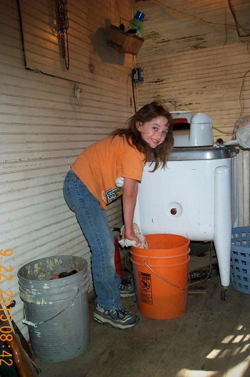 Once a load has been washed, items are first wrung and then put a couple at a time into a bucket of rinse water.