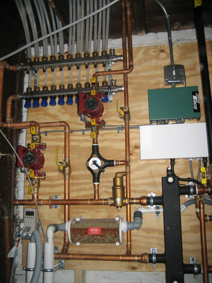 At top, a PEX distribution manifold co-exists right along with copper and other plumbing fixtures to service a boiler and radiant under floor heating system. CCL C