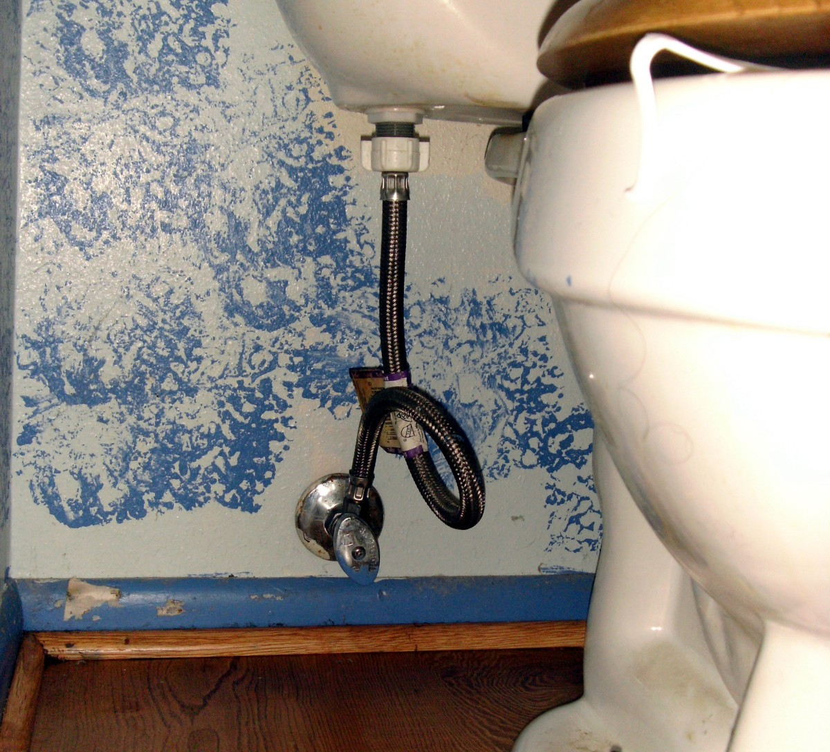 Location of the water valve and hose to the toilet tank.  This hose is braided metal; a good idea as it is not likely to ever burst.
