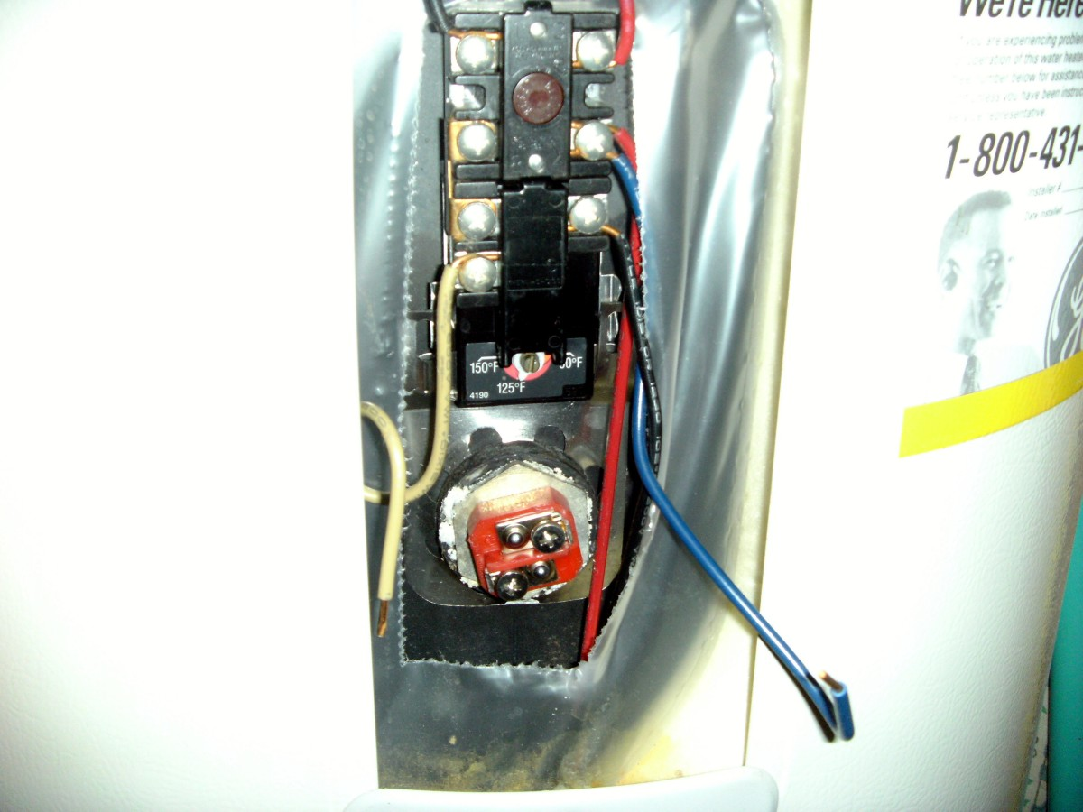 Plastic cover removed, leaving the upper thermostat and heating element.  Note the adjustment screw at the bottom of the thermostat.  This heating element is the red colored square with a silver hex nut around it. at the bottom of the opening.