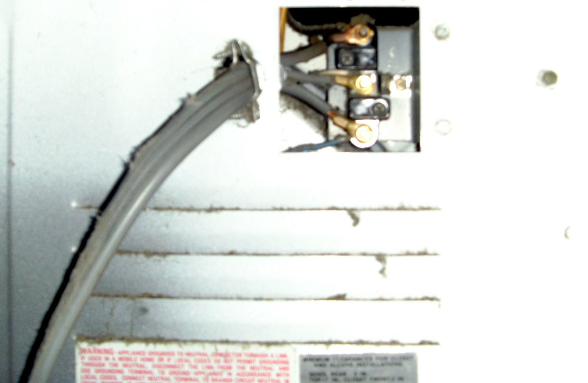 The cover plate on the back of the dryer has been removed, exposing the wire termination block.  Notice the clamp holding the wire to the dryer.