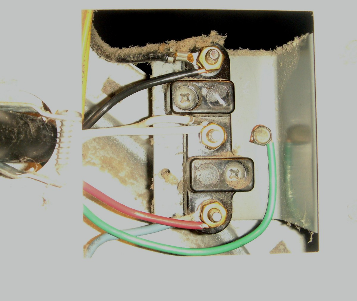 The white wire is placed on the center terminal, where it belongs.  The ground strap has been removed and the green wire attached to where it mounted on the frame of the dryer.