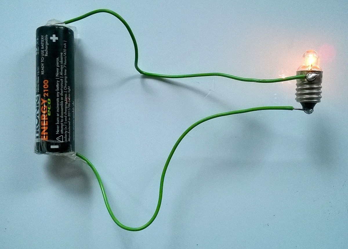 An AA cell forces current through the wires and lights up a bulb in this example of a simple circuit.