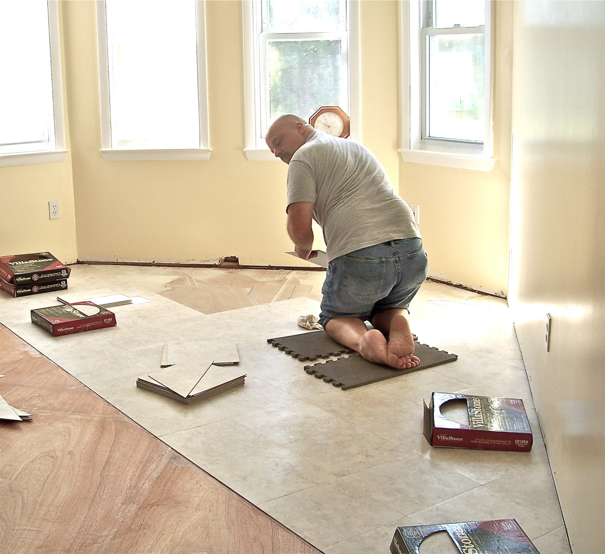 Kitchen Floor in Progress - We decided to lay tiles at an angle. Here my son Jeff is laying the floor tiles.