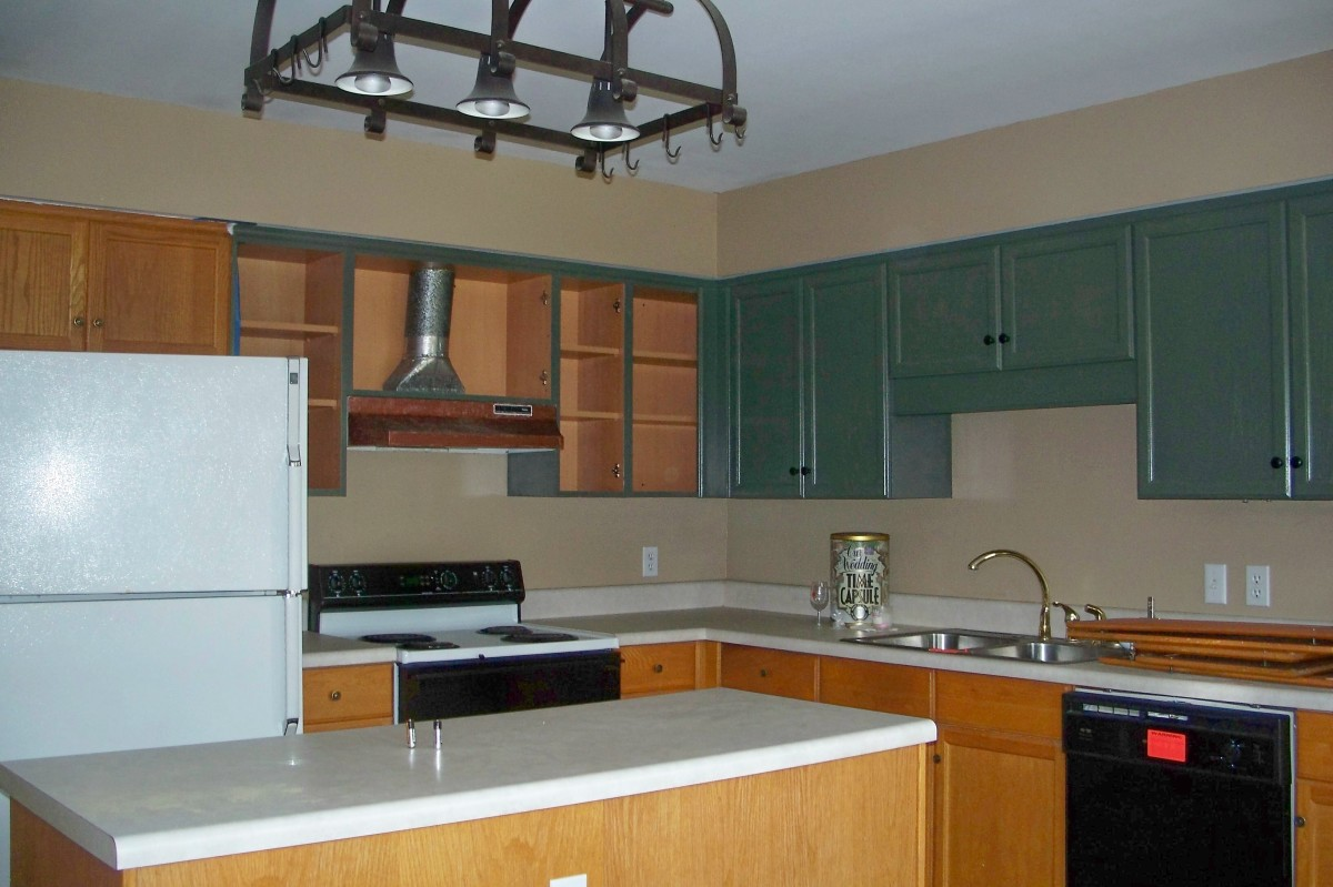 BEFORE: Cabinets were mix of painted and natural wood. Some hardware missing and mismatched. Stove hood copper colored.