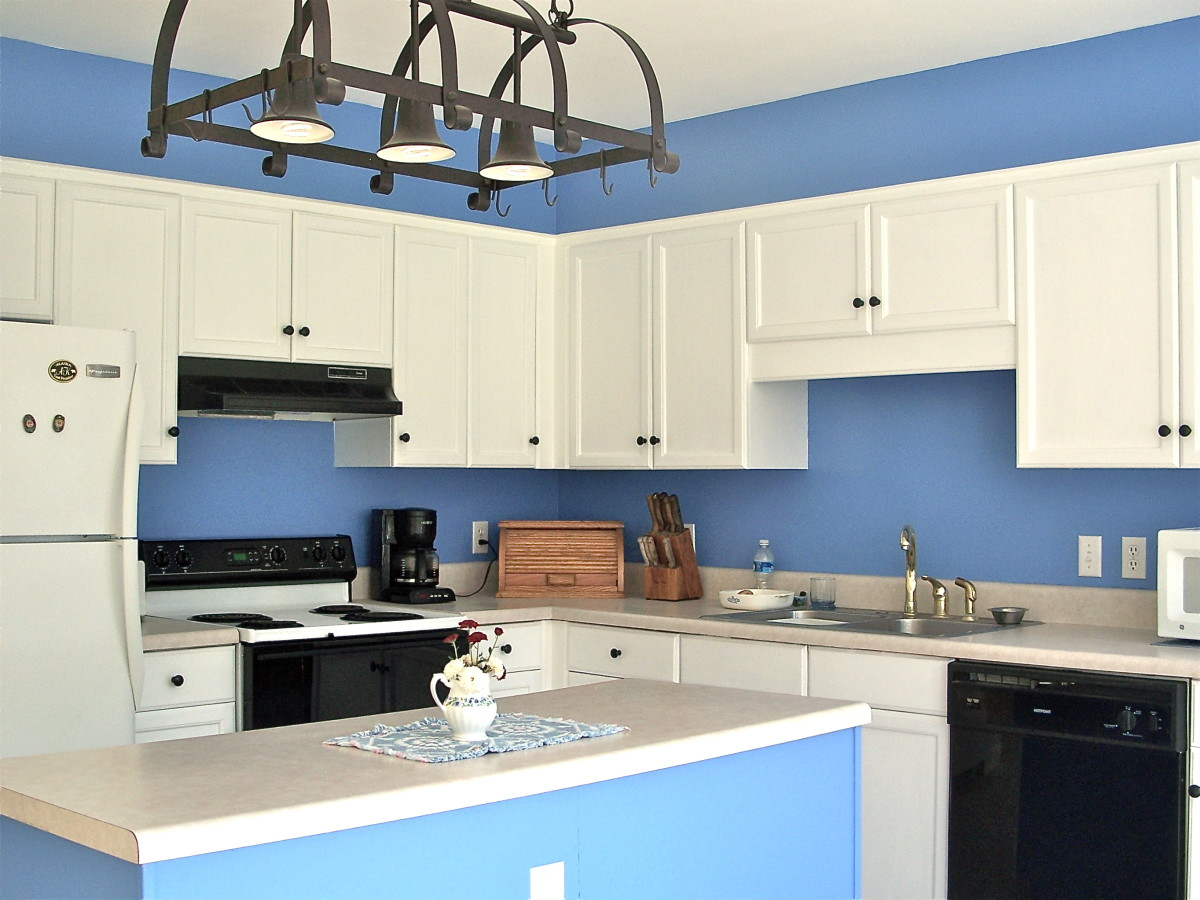 Cabinets painted white, backsplash and cornice over cabinets blue.Stove hood repainted glossy black.